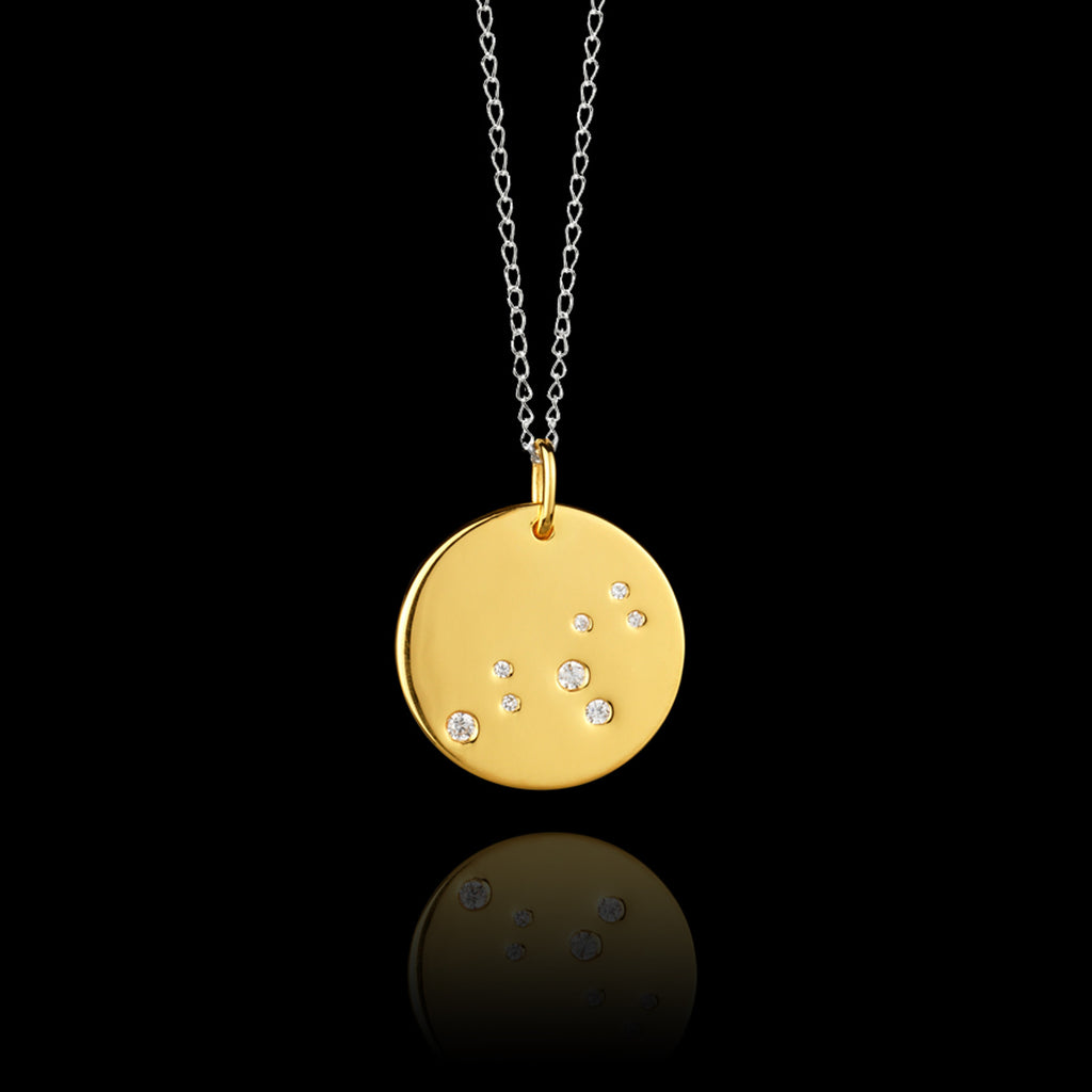Close up of Leo Zodiac star sign pendant in gold with silver chain. Made by British jewellery designer Catherine Zoraida