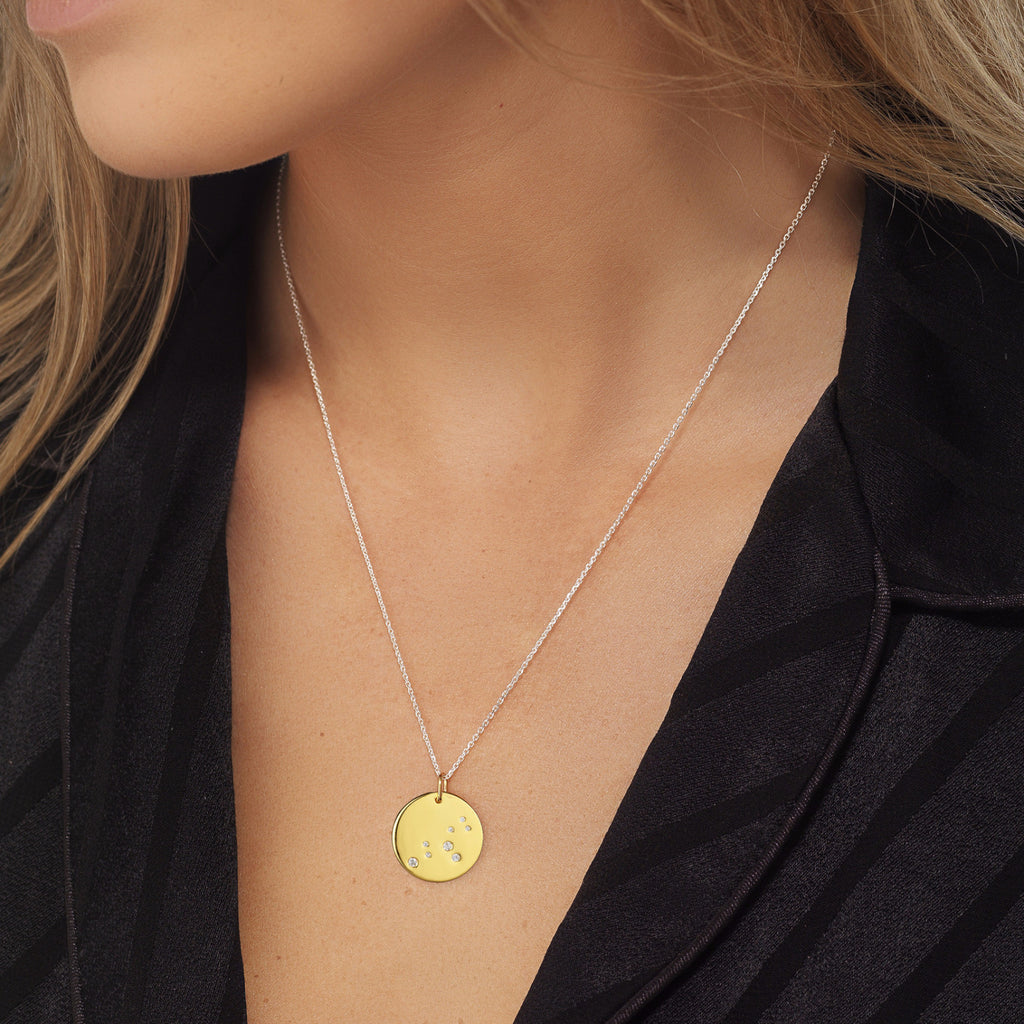 Leo Zodiac star sign pendant in gold with silver chain. Model Lucy Williams