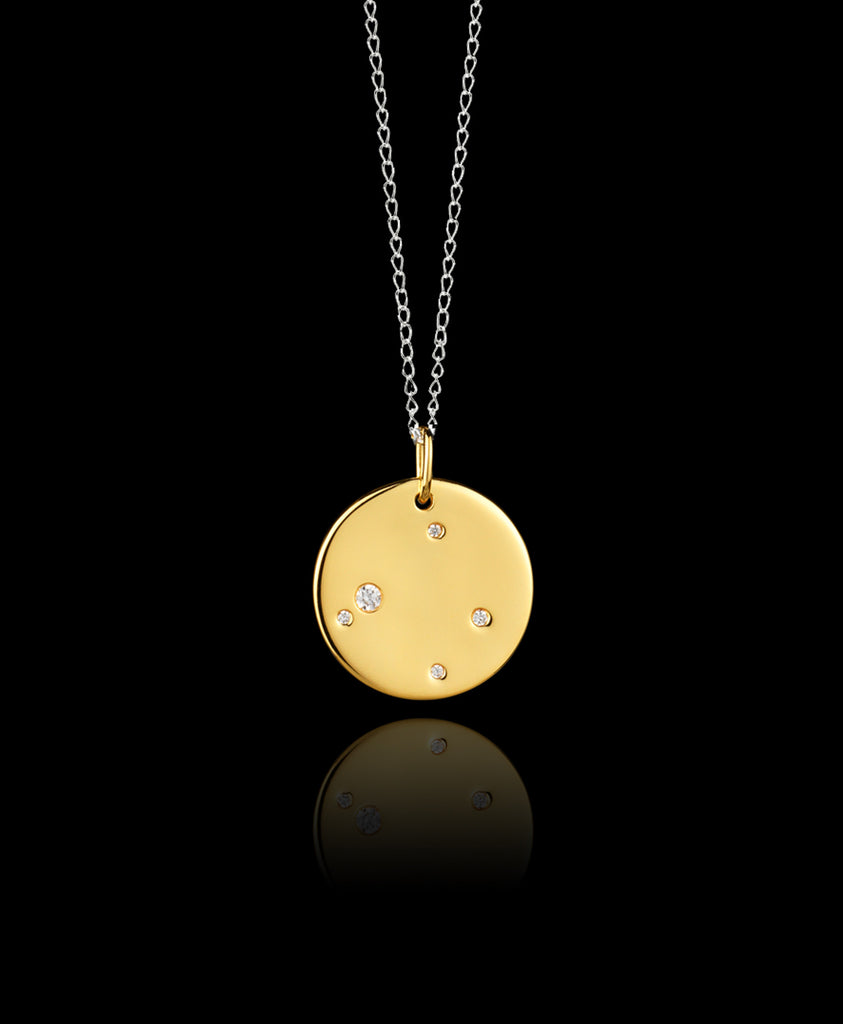 Close up of Libra Zodiac star sign pendant in gold with silver chain. Made by British jewellery designer Catherine Zoraida