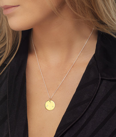 Libra Zodiac star sign pendant in gold with silver chain. Model Lucy Williams