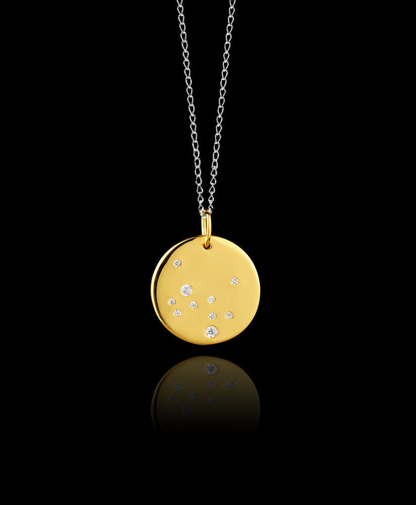 Close up of Sagittarius Zodiac star sign pendant in gold with silver chain. Made by British jewellery designer Catherine Zoraida