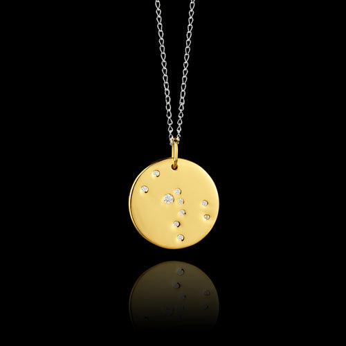 Close up of Taurus Zodiac star sign pendant in gold with silver chain. Made by British jewellery designer Catherine Zoraida
