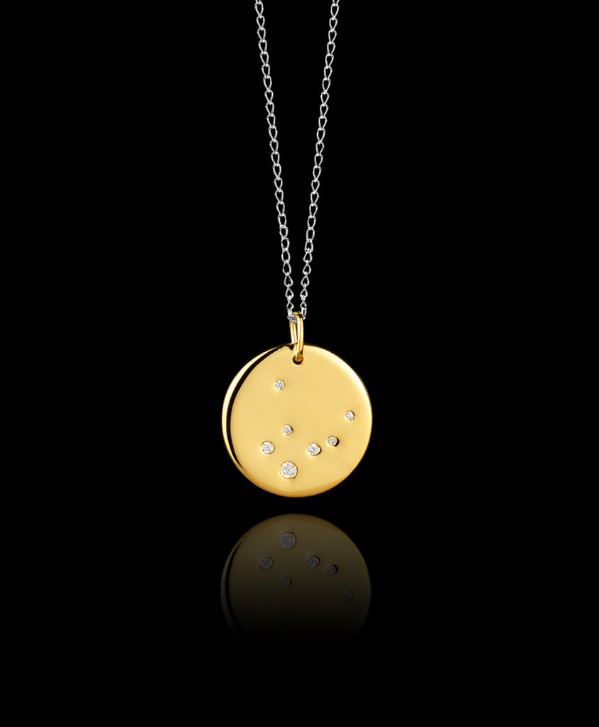 Close up of Virgo Zodiac star sign pendant in gold with silver chain. Made by British jewellery designer Catherine Zoraida