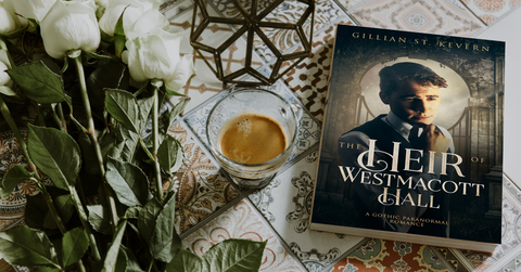 The Heir of Westmacott hall in print form is laid on a table, beside a cup of tea and a bunch of white roses.