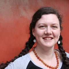 portrait of Gillian, with her hair in plaits, a red necklace and grey t-shirt, standing in front of a red wall.
