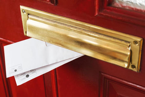 Two envelopes poke out of a polished brass post box on a red door.