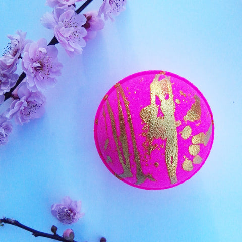 Bright neon pink round bath fizzy with gold glitter in a random splatter effect on top half