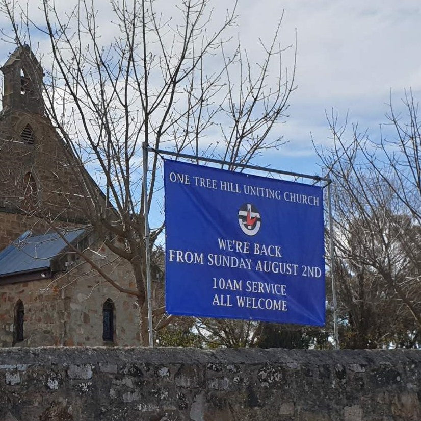 Blue outdoor banner with logo suspended by 4 eyelets in front of church