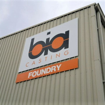 Large ACM sign with company name and logo on warehouse wall