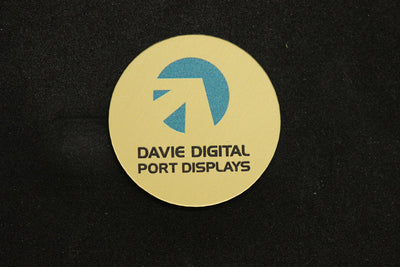 Brushed gold plastic circle badge with blue and black printed logo