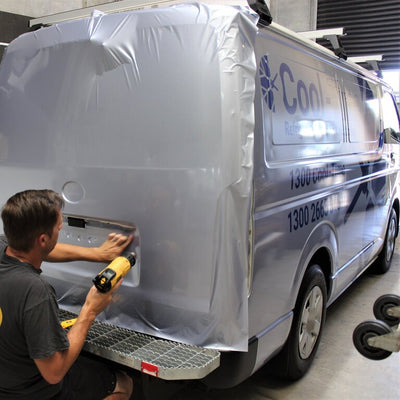 Application of a full vehicle wrap in our Port Adelaide workshop. Dureable silver vinyl and business details in large blue lettering on a fleet van