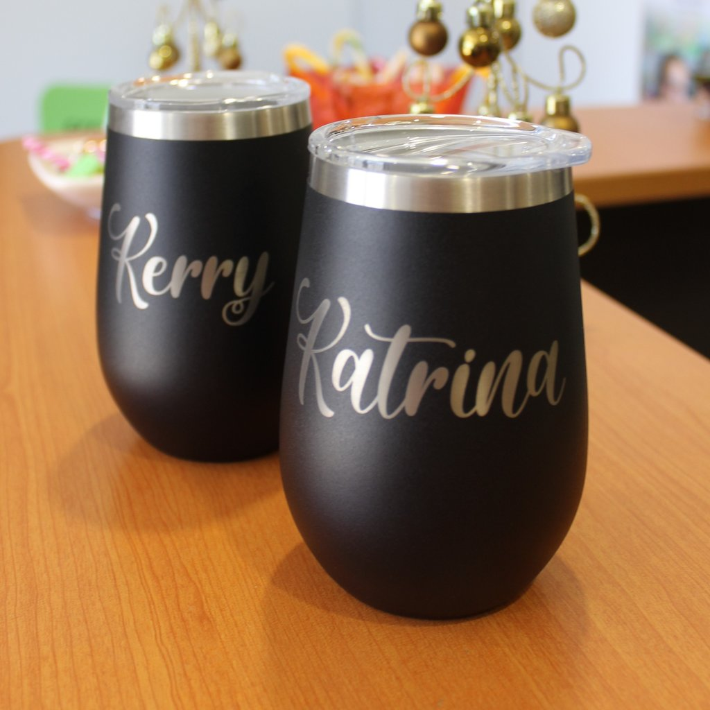 Laser engraved travel tumblers for corporate christmas gifts. Gold text on texured black metal