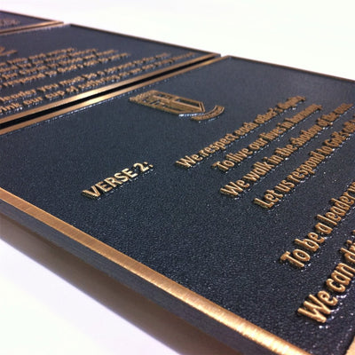 Bronze metal plaque with stipple texture and raised text