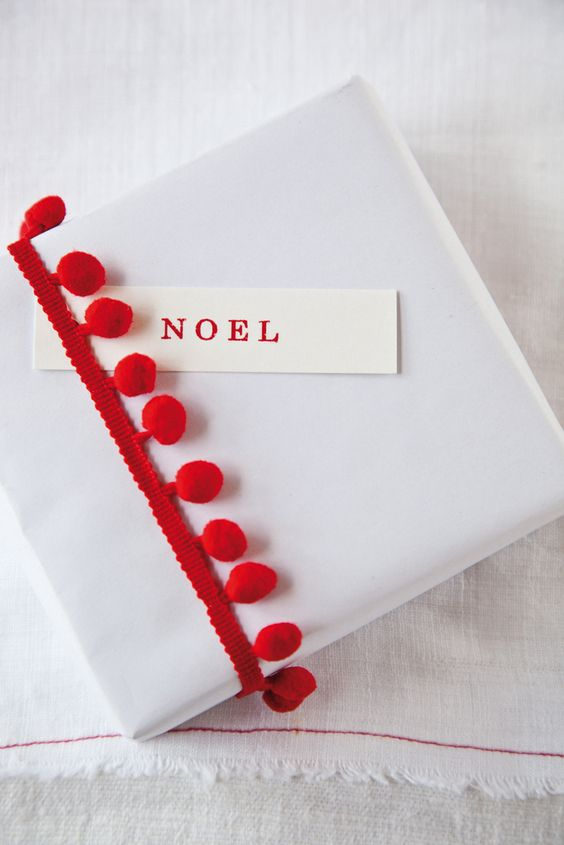 Here's a simple idea from  Cox & Cox : wrap in plain white paper and add a pom-pom bobble trim, available at most craft and haberdashery shops.