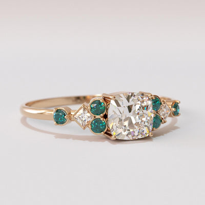 White sapphire ring with emerald side stones.