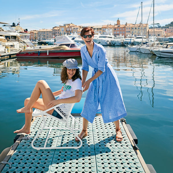 Two beautiful women on a dock laughing. One is seated in a Fermob Sixties outdoor chair.