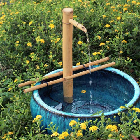 Adjustable bamboo fountain in a blue ceramic bowl in a field of flowers.