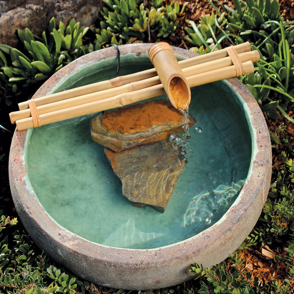 Three-arm bamboo fountain in a ceramic bowl.