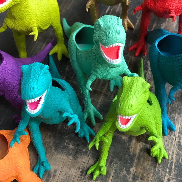 An army of T. Rex dinosaur planters in bright colors.