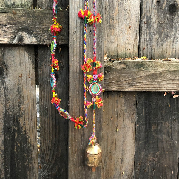 Colorful thread and mirror garland with brass bell.