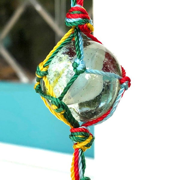 Close up of marble in colorful hanging garden mobile.