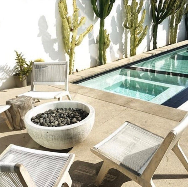 A concrete bowl fire pit near a pool and garden designed by King Garden Design
