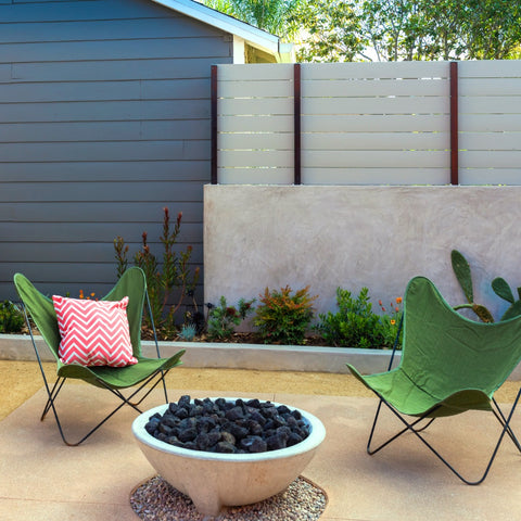 Cazo concrete fire pit with two green butterfly chairs on decomposed granite in a garden.