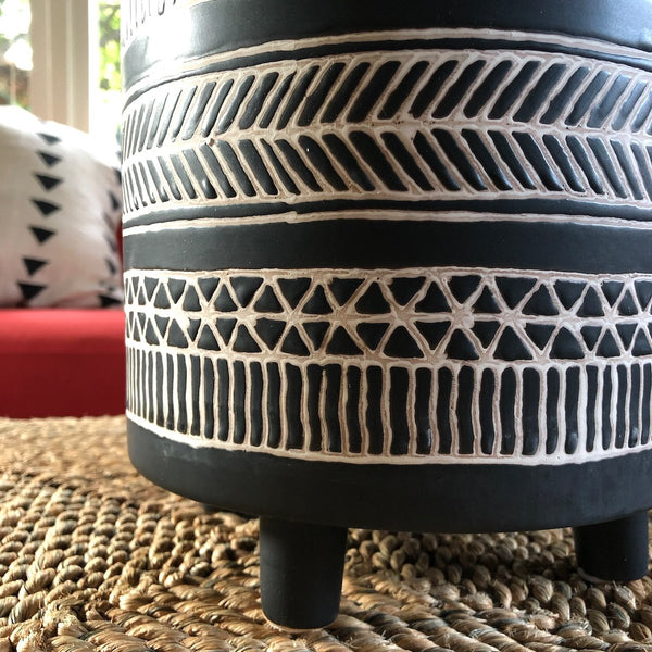 Close up of matte black planter with white lines in a tribal pattern.