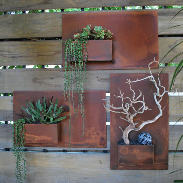 Three rusted iron City Planters on a modern wood fence planted with succulents.
