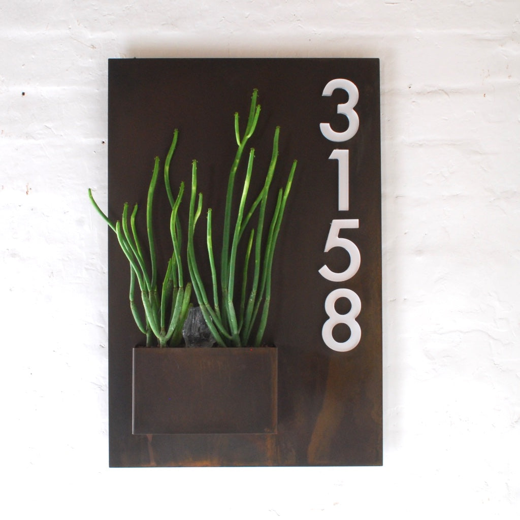 Vertical rusted iron City Planter planted with senecio and showing street numbers.
