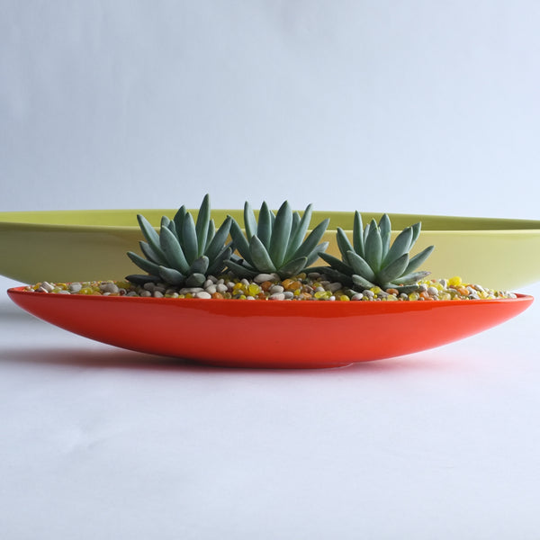 Orange Bauer Canoe planter filled with succulents.
