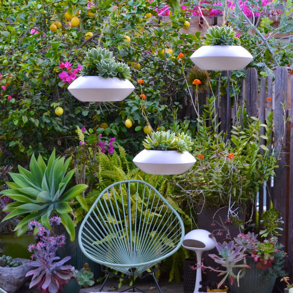 Three Orbit Hanging Planters staged in a chandelier effect with an Acapulco chair in the background.