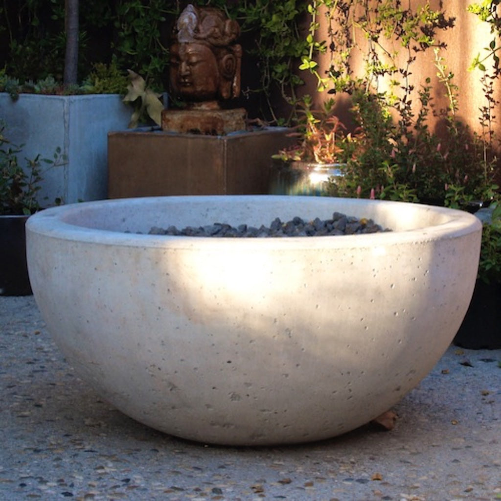 Concrete bowl fire pit filled with lava rock.
