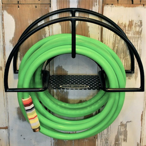 Hose jockey mounted on a wall with green hose.