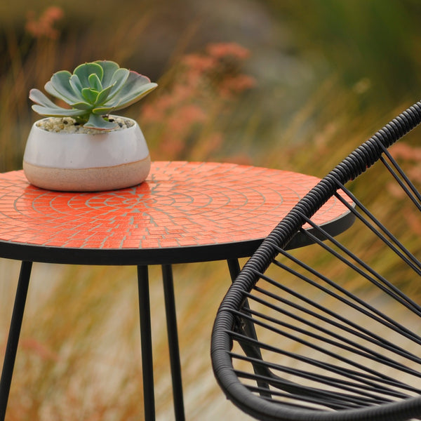 Orange Midge tiled table next to a black Acapulco chair with a Petersen Pottery planter on top.
