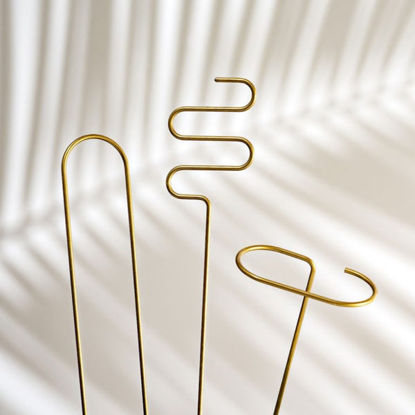Set of three brass plant sticks.