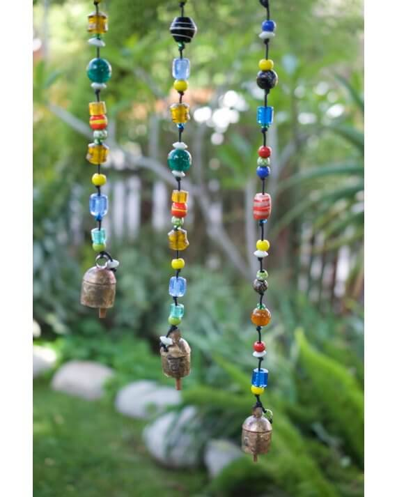 Three multi colored glass bead garlands hanging in a tree.