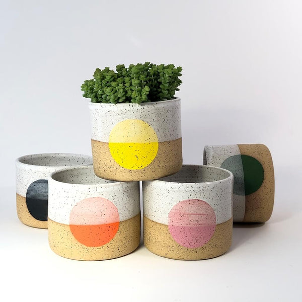 A collection of handmade pots by Double M pottery with various colored dots.