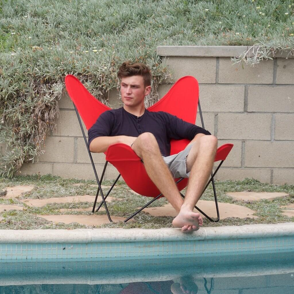 Red butterfly chair with handsome young man sitting on edge of a pool.