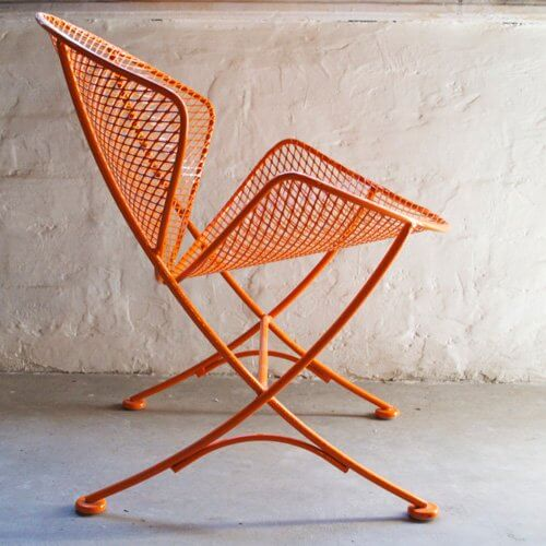Side view of an orange metal mesh clam chair.