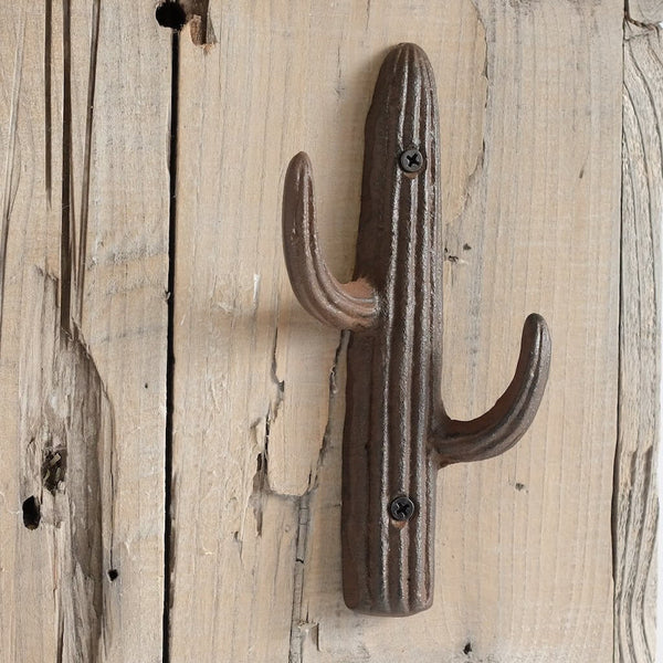 Saguaro cactus shaped iron hook on a wood paneled wall.