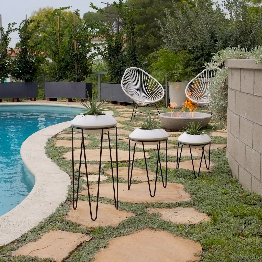 Set of three Hairpin leg plant stands with white orbit planters by a swimming pool.