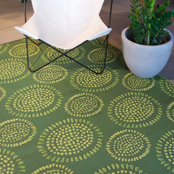 Recycled plastic Molly rug by Mad Mats with a white Acapulco chair on top.