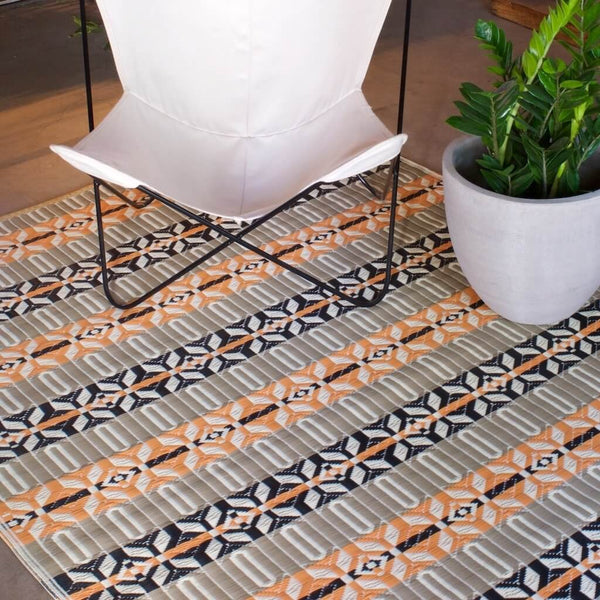 Moroccan Mad Mat in Brick color with a white Butterfly Chair on top.