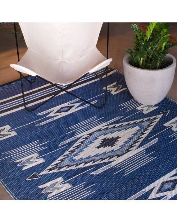 Mad Mats Navajo Blue outdoor rug with a white butterfly chair on it.