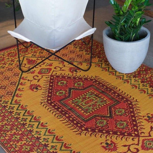 Rust Mad Mats Oriental Turkish outdoor rug with a butterfly chair on it.