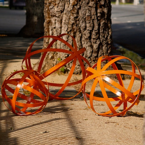 "Set of three iron spheres powder coated orange and used as garden art in 30"", 24"" and 18"" size."