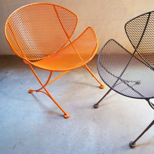 Two mid-century modern mesh metal chairs in orange and black.