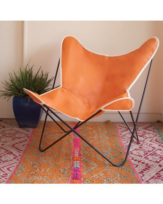 Orange with natural trim butterfly chair on rug.