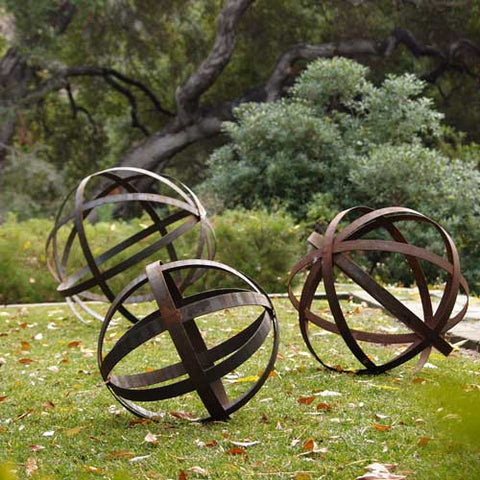 Rusted iron spheres as garden art on a lawn in front of an oak tree.
